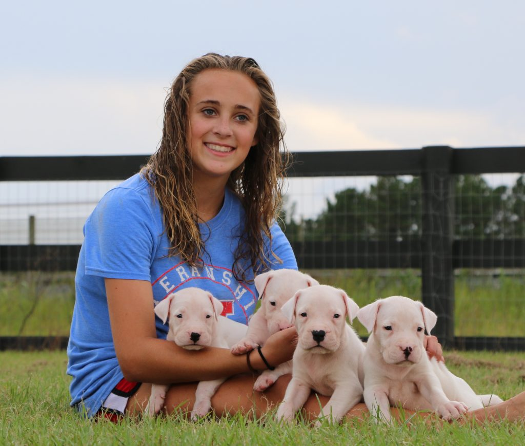 Girl sitting with white puppies
