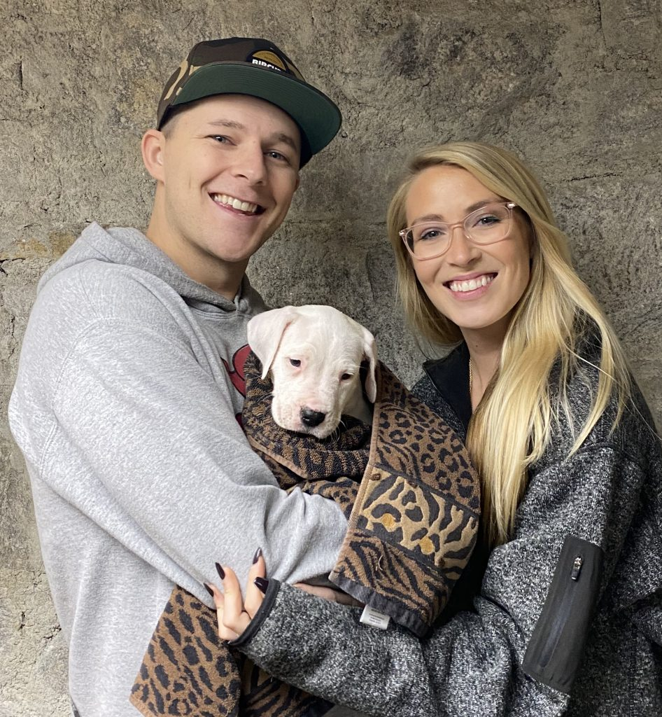 Man and woman holding their puppy